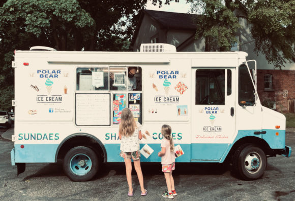 Photo of Lily and Beatrix deciding what to order from an ice cream truck in summer